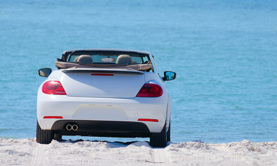 White convertible automobile with the top down at the beach on a sunny day with a soft blue water background