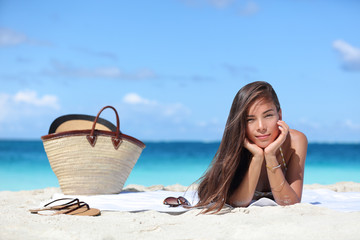 Woman relaxing on beach vacation summer holidays. Beautiful Asian girl lying down on towel with straw hat and flips flops on white sand tanning. Sun hair and skin care concept.