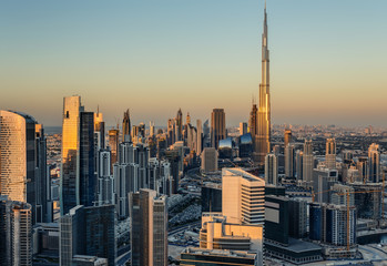 Beautiful modern city architecure at golden sunset. View of Dubai's business bay towers.
