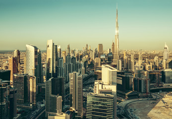Beautiful architectural background. Panorama view of Dubai's business bay towers at sunset.