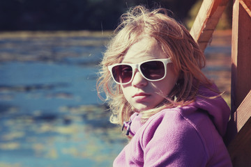 Blond teenage girl in sunglasses sitting on river coast