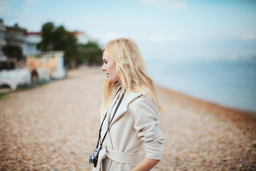 blonde girl in a coat with a camera on a pebble beach