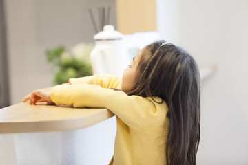 カウンターキッチンに肘をつく女の子