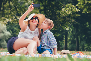 Mother with son take a selfie photo in summer park