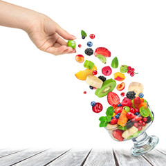 fresh fruit salad with ingredients in the air in a glass bowl on