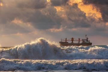 Sun setting at the sea with sailing cargo ship