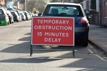 Temporary Obstruction 15 Minutes Delay sign on residential road