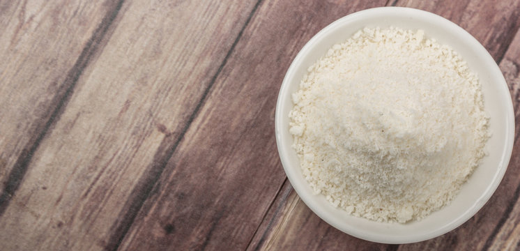 Dried coconut powder in white bowl over wooden background