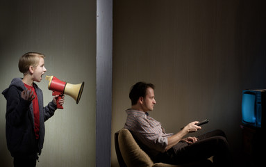 Man watching TV while his son calling him through a megaphone. Lack of father's attention concept Wall mural