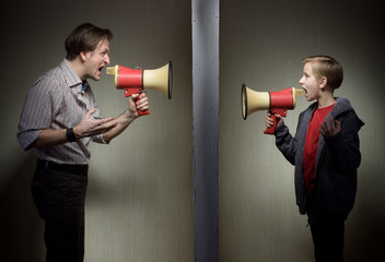 Tween son and his father yelling through the megaphones standing on either side of a wall