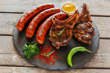 Aluminium Prints Grill / Barbecue Grilled sausages and steak on the bone barbecue