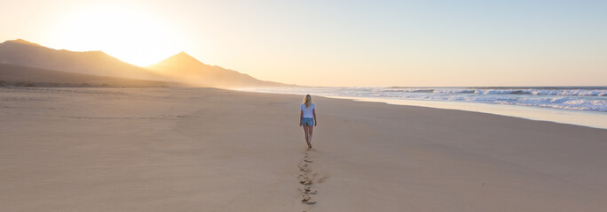Woman walking on sandy beach in sunset leaving footprints in the sand. Beach, travel, concept. Copy space. Panoramic composition.