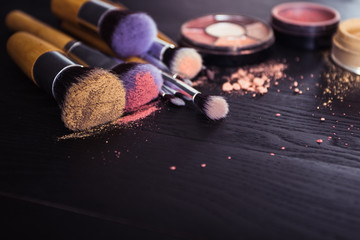 make up brushes with powder and rouge on a black wooden background