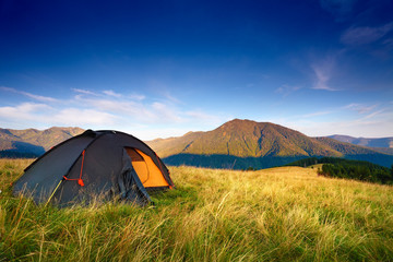 Poster Hill camping tent on the mountain meadow