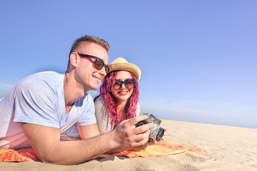 Two guys having fun with old vintage retro camera on tropical beach - Cool trendy modern hipster young couple on holidays vacation - Happiness and travel lifestyle concept - Tilted horizon composition