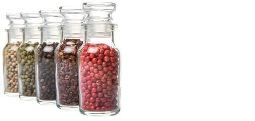 Szechuan peppercorns, green peppercorns, white peppercorns, black peppercorns and pink peppercorns in glass vial over white background