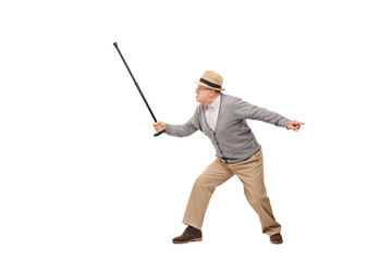 Angry senior holding his cane as a sword