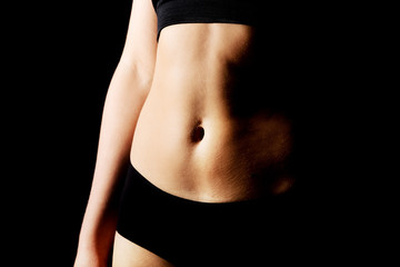 Belly of slim young woman in black sports underwear