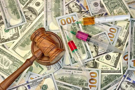 Judges Gavel And Syringe With Injection On Dollar Cash Backgroun