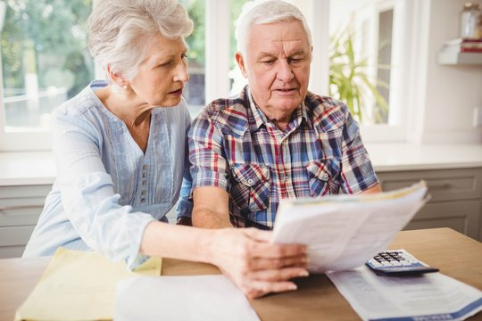 Worried senior couple checking their bills