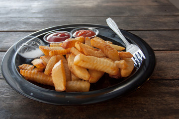 French fries on the plate on a wooden table in a fast food cafe