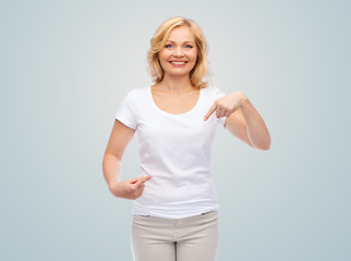 smiling woman in white t-shirt pointing to herself