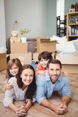 Portrait of smiling family lying on hardwood floor