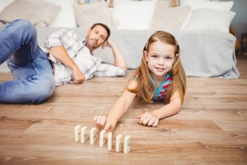 Happy girl arranging domino by father on hardwood floor