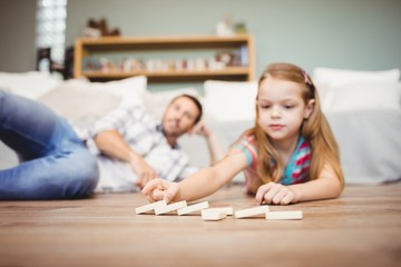 Girl arranging domino while father lying on hardwood floor