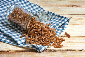 wholemeal pasta falling out of a glass jar on a blue patterned kitchen towel