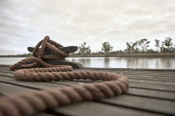 Rope tied to a mooring cleat on a floating wooden dock on the river.