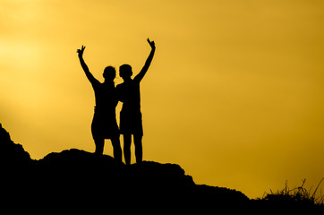 Silhouette of a couple making the sign of victory on top of a hill