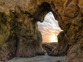 Ghost - The sea sculpted a natural arch in the shape of a ghost. The sunset spills through the archway off the Pacific Ocean coastline in Laguna Beach, California.