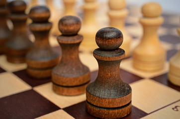 A squad of black pawns on chessboard. Figures stand in a row. Selective focus, close up view. Vintage toning.