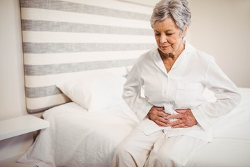 Senior woman suffering from stomach ache sitting on bed