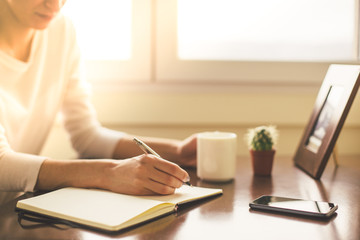 Cropped shot of woman writing and holding coffee cup