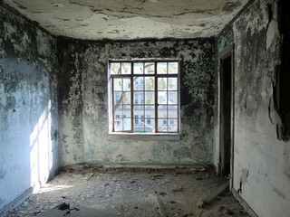 Depressing abandoned room with centered window - landscape color photo