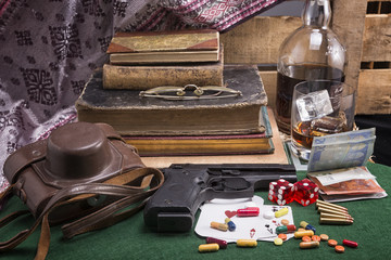 Set of ancient books , whiskey, casino dice and cards with handgun and bullets . Addictions , gambling, drinking and firearms. Dangerous lifestyle