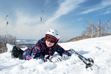 Girl skier lying in snow on mountain top