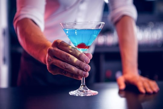 Bartender serving a blue martini