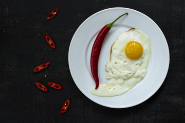 Fried eggs on white plate with red hot pepper on black background