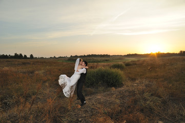 Bride and Groom in the Field at Sunset