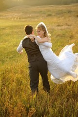 Bride and Groom Posing in the Field against sunbeams