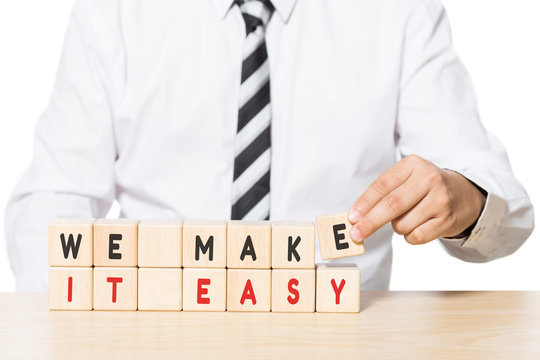 Businessman Arranging Wooden Blocks with we make it easy words