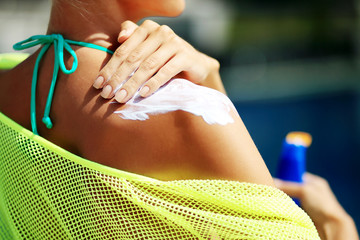Woman applying sunblock protection on shoulders