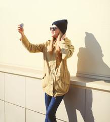Fashion pretty woman makes selfie portrait on smartphone in sunn