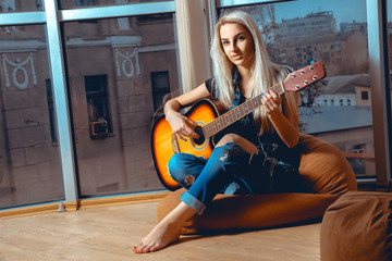 Beauty young blonde lady plays guitar