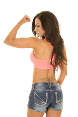 woman in denim shorts and pink sports bra back flex