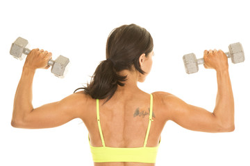 woman in green sports bra and purple shorts flex weights back