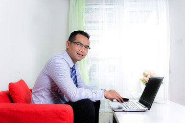 Smile asian business man using laptop computer in his home